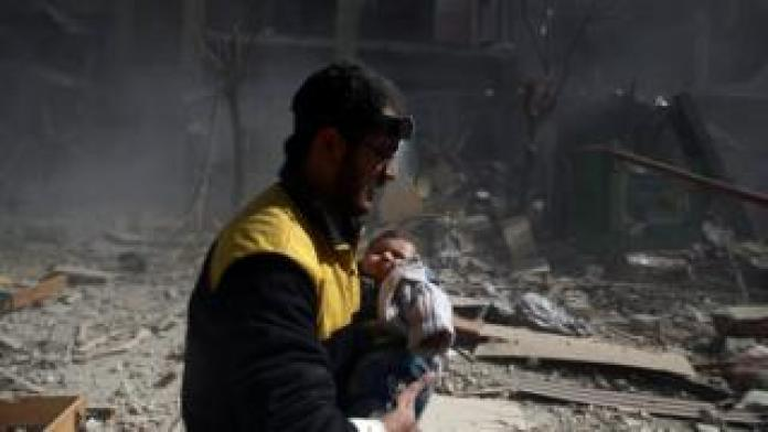 Amid rubble and smoke, a man wearing a headlamp and yellow jacket carries a baby in distress