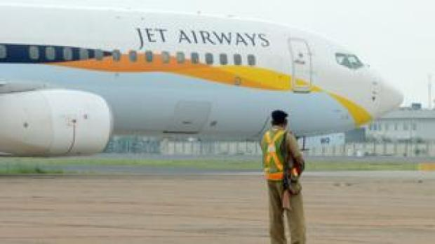 An Indian security official looks on as an aircraft of Jet Airways taxies after landing at Indira Gandhi International Airport in New Delhi on September 12, 2012