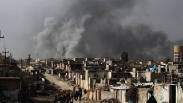 """Iraqi families leave Mosul""""s Nablus neighbourhood on March 12, 2017, during an offensive by security forces to retake the western parts of the city from Islamic State (IS) group fighters."""