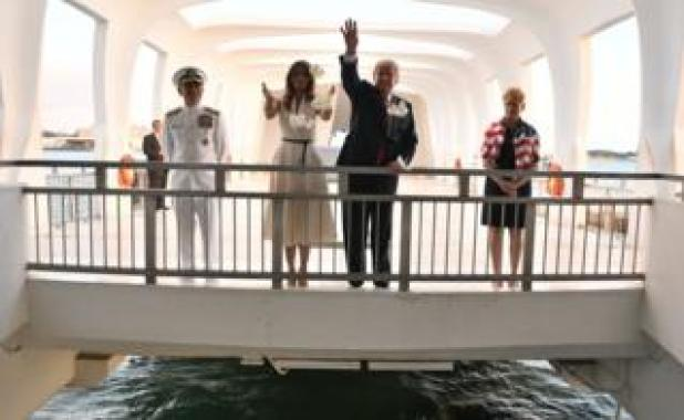 US President Donald Trump and First Lady Melania Trump throw flowers during their visit to the USS Arizona Memorial on November 3, 2017