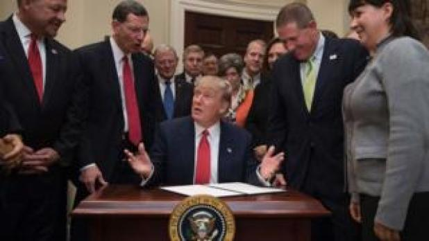 President Donald Trump (C) prepares to sign the the Waters of the US (WOTUS) executive order.