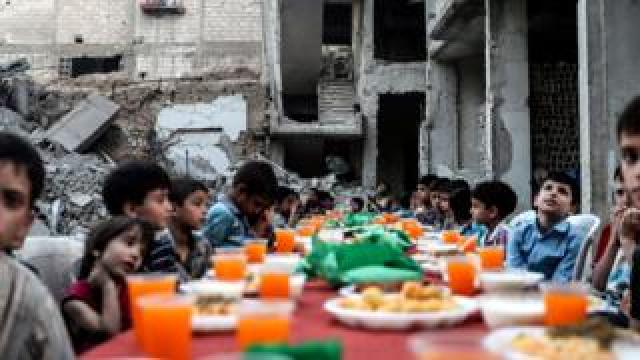 Children sit at a table as they wait for Iftar, evening meal at the end of daily Ramadan fast at sunset, next to rubble and destroyed houses, which were damaged after air strikes, in Douma, Syria, 17 June 2017.