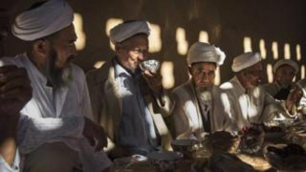 Uyghur men gather for a holiday meal during the Corban Festival on 13 September, 2016 in Turpan County, in the far western Xinjiang province, China