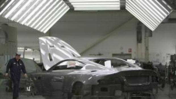 A man works on an Aston Martin