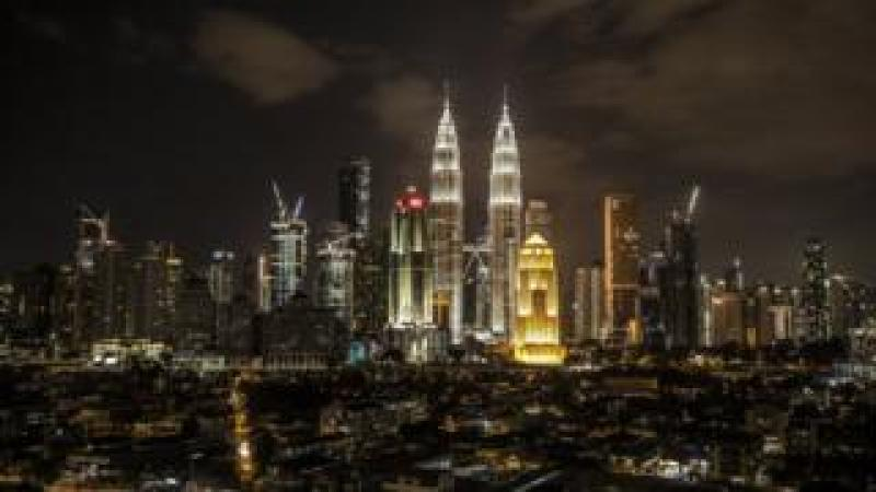 A view of the Petronas Towers (C) with light on before Earth Hour in Kuala Lumpur, Malaysia
