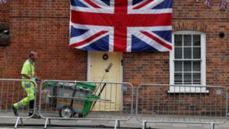 A street cleaner walks past a house decorated in bunting and a Union flag in Windsor