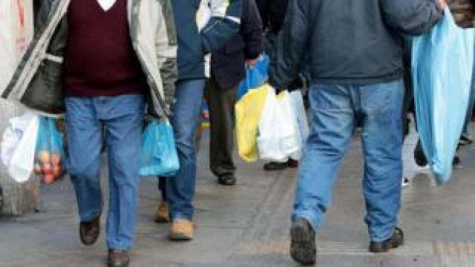 Consumers carry plastic bags on a street of central Athens