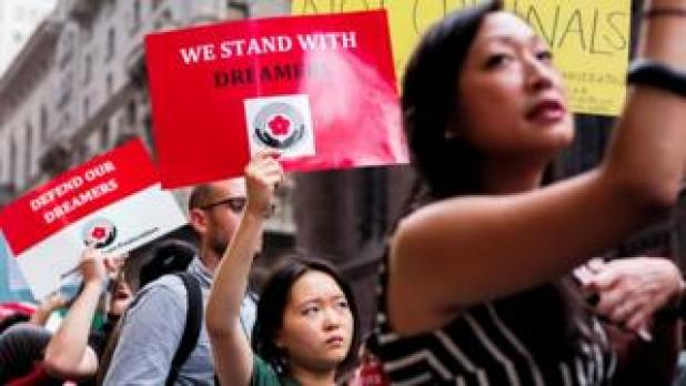 Protesters hold up signs during a demonstration against US President Donald Trump during a rally in support of the Deferred Action for Childhood Arrivals (Daca) in New York, 5 October