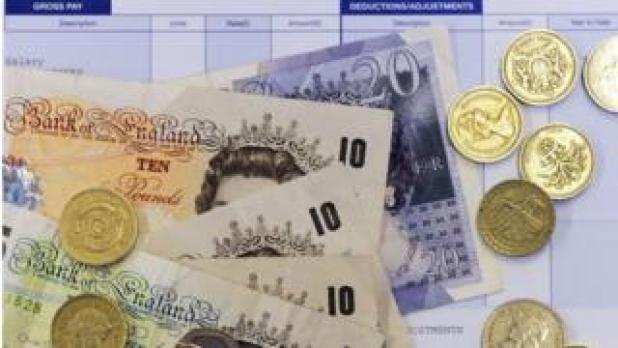 pound coins and notes on pay slip