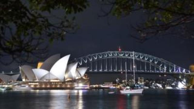Sydney Harbour Bridge and the Opera House are seen before being plunged into darkness for the Earth Hour environmental campaign on 24 March 2018.