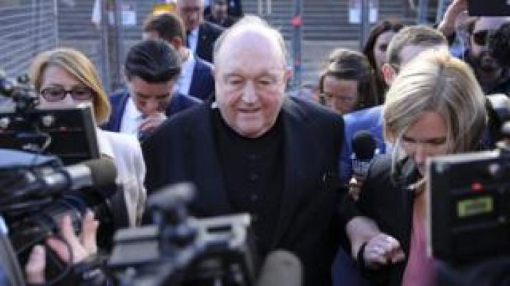 Archbishop Philip Wilson leaving court, surrounded by reporters