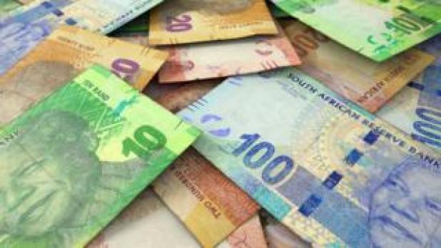 A macro close-up view of a messy scattered pile of South African rand banknotes