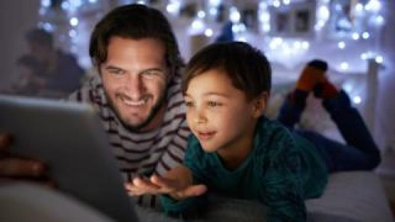 Father reading an iPad story to his son
