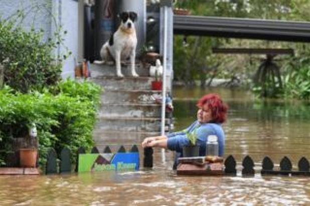 A woman attempts to access her home as her dog looks on in central Lismore, New South Wales, Australia, 31 March 2017.