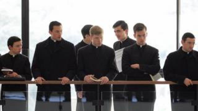 Priests and seminarists wait in the hall of the Regina Apostolorum pontifical university in Rome for the first lesson on exorcism, 17 February 2005