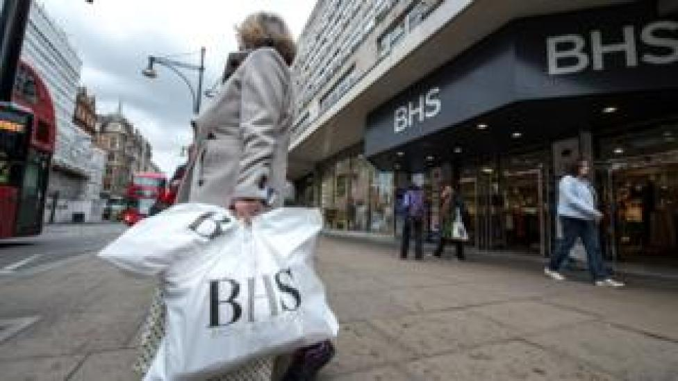 Shopper carrying BHS bags outside BHS store