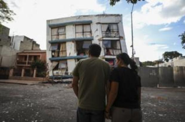 Man and woman stood in front of a damaged building. What used to be a five-storey block has lost its bottom two levels entirely.