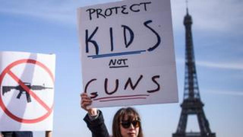"A woman holds a poster which read ""Protect Kids not Guns"" as French and Americans gather near the Eiffel Tower on the Trocadero square in support of the US ""March For Our Lives"" movement, in Paris, France,"