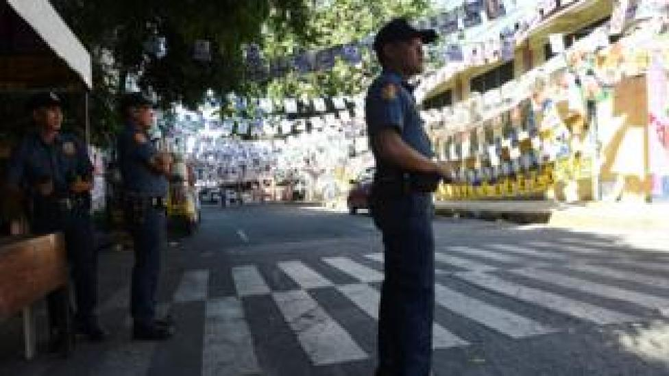 policemen standing outside polling station, with election bunting lining the street