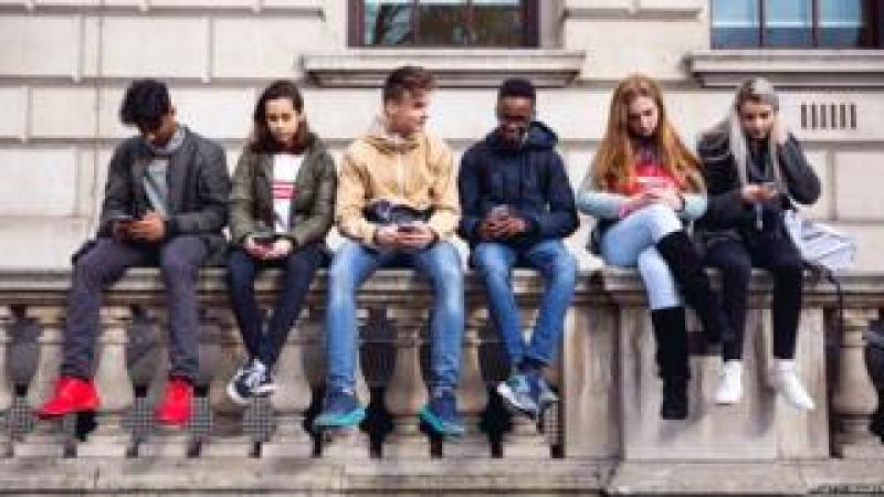 Students sitting on a wall