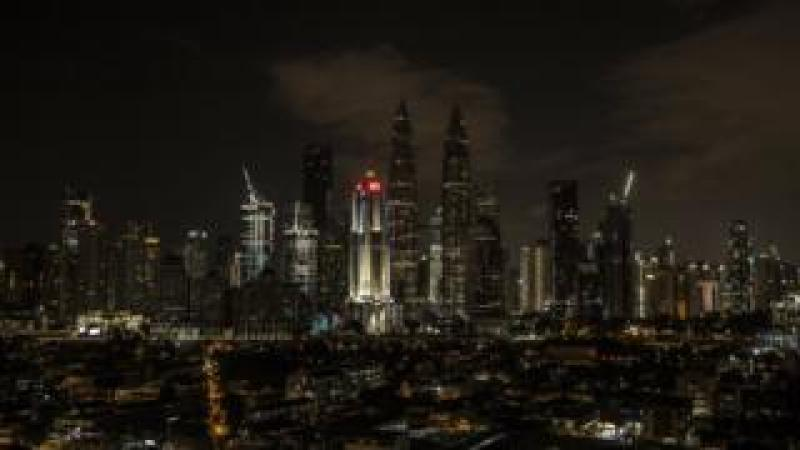 A view of the Petronas Towers (C) with light off during Earth Hour in Kuala Lumpur, Malaysia
