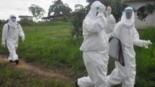 Health workers leave after they took a blood specimen from a child to test for the Ebola virus in a area were a 17-year old boy died from the virus on the outskirts of Monrovia, Liberia, Tuesday, June 30, 2015