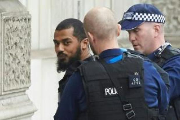 Firearms officers from the British police detain a man on Whitehall near the Houses of Parliament in central London