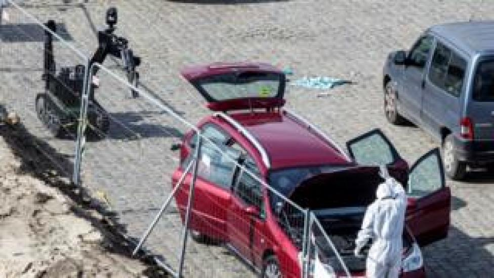 A forensics expert stands next to a car which had entered the main pedestrian shopping street in the city at high speed, in Antwerp, Belgium, 23 March 2017