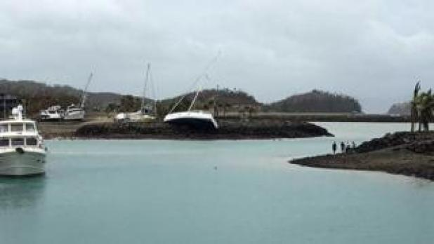 A boat (C) ran aground on Hamilton Island after strong Cyclone Debbie hit the Whitsundays Islands in Queensland on March 29, 2017