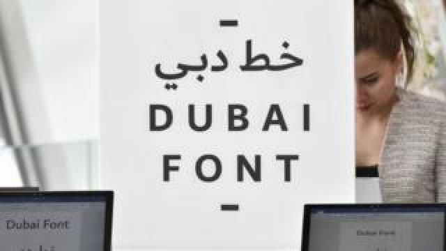 An attendee looks at computers showing the 'Dubai Font'