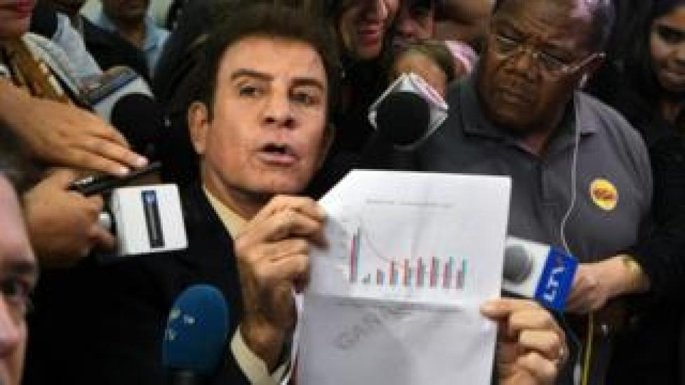 """The presidential candidate for Honduras"""" Opposition Alliance against the Dictatorship, Salvador Nasralla (centre L), gestures as he meets with coordinator of the Electoral Supreme Tribunal, Leticia Henriquez (not pictured), to present a document asking to annul the results of the still-unresolved November 26 vote"""