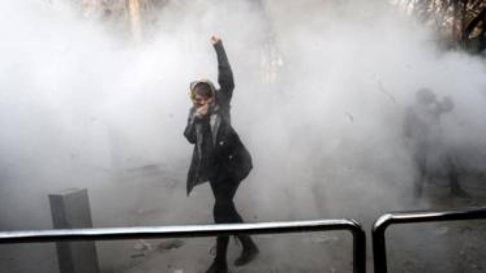 An Iranian university student raises her fist in a cloud of smoke at Tehran University