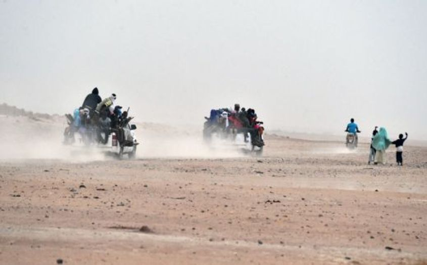 A woman and children wave to migrants sitting on pick-up trucks, holding wooden sticks tied to the vehicle to avoid falling from it, as they leave the outskirts of Agadez for Libya
