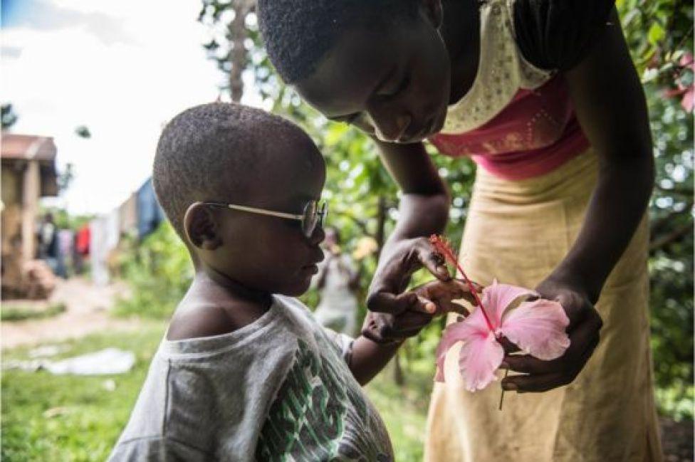 La prima de Criscent le enseña una flor.