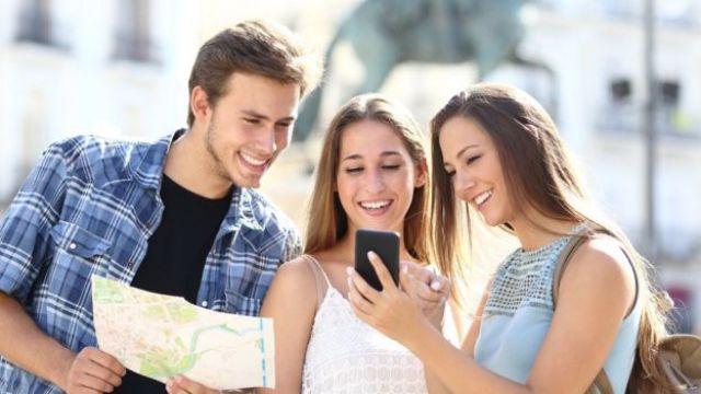 Grupo de 3 jovens com mapa e celular em mãos