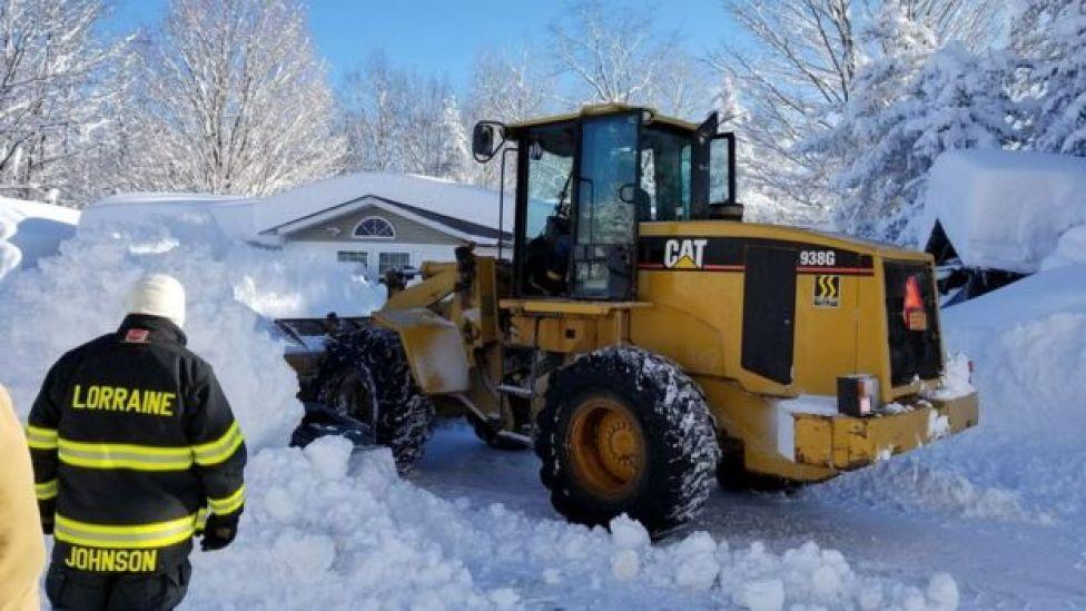 Bomberos removiendo nieve para rescatar a una mujer atrapada, en Lorraine, Nueva York.