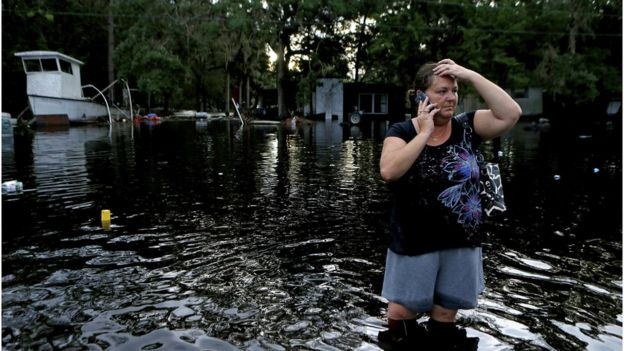 Lynne Garrett speaks to loved ones on the phone as she surveys damage outside of her home from the winds and storm surge associated with Hurricane Hermine which made landfall overnight in the area on 2 September 2016 in Tampa, Florida