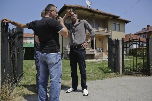Fadil Segashi, uncle of Armela Segashi, one of the victims fatally shot at the Olympia shopping mall in Munich, gestures as family members gather, in the town of Podujevo, Kosovo on Saturday, 23 July