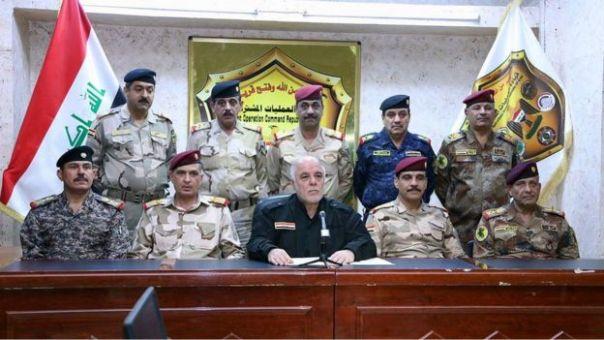 El primer ministro iraquí Haider al-Abadi, al centro, rodeado por militares al hacer el anuncio de la ofensiva en Mosul.