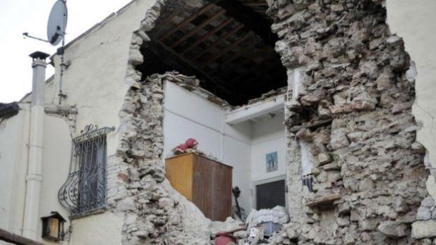 Una pared de una casa derrumbada deja ver la sala