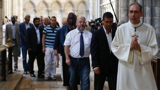 fieles musulmanes a pie detrás de un hombre religioso ya que asistir a una misa en homenaje al sacerdote Jacques Hamel en la catedral de Rouen el 31 de julio el año 2016