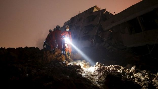 Firefighters use torches to search for survivors among the rubble of collapsed buildings after a landslide hit an industrial park in Shenzhen, Guangdong province, China December 20, 2015. R