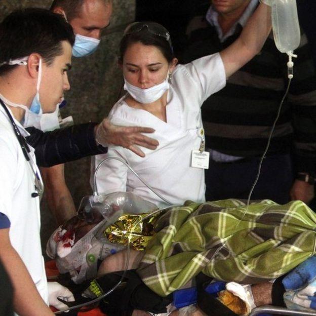 Periodista Rafael Henze siendo trasladado en una camilla