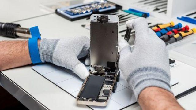 Imagem mostra homem fazendo reparos em smartphone