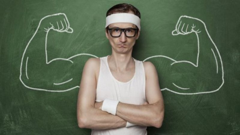 Un hombre de espaldas a una pizarra con brazos musculosos dibujados.