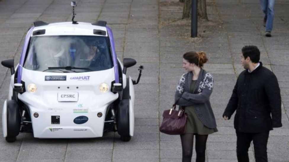 A man and woman look at a self-driving car