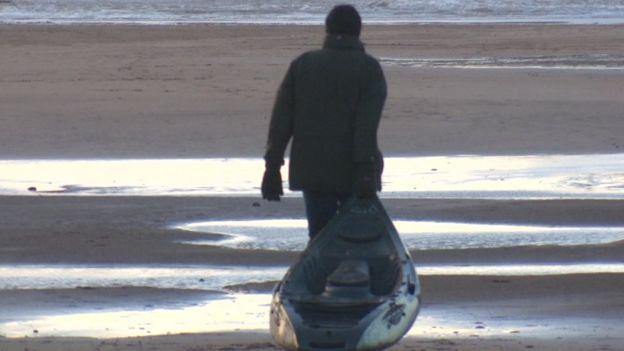 man dragging kayak