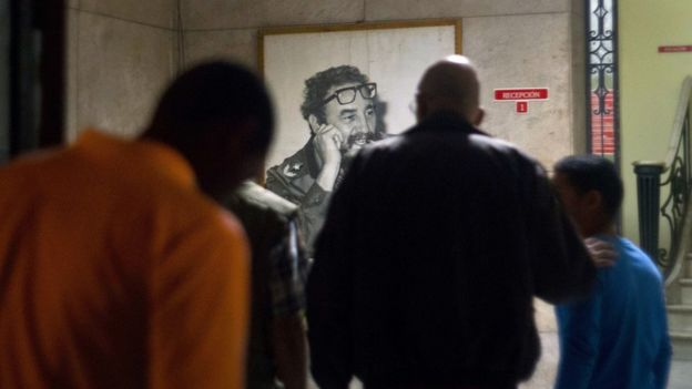 Cubans gather in front of a portrait of Fidel Castro