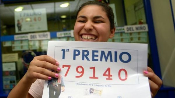 Winner Imanes Naamane celebrates as she holds a placard showing the first prize winning number, 79140, of Spain's Christmas Lottery