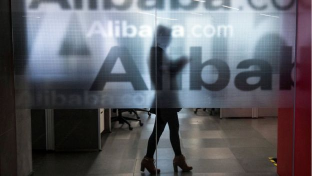 An employee is seen behind a glass wall with the logo of Alibaba at the company's headquarters on the outskirts of Hangzhou, Zhejiang province, 23 April 2014.